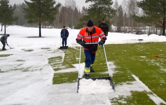 Kolan kanssa greeniltä lunta pois työtävä Kalevi Kronholm on tehnut TG:ssä talkoita jo neljänkymmen vuoden ajan.