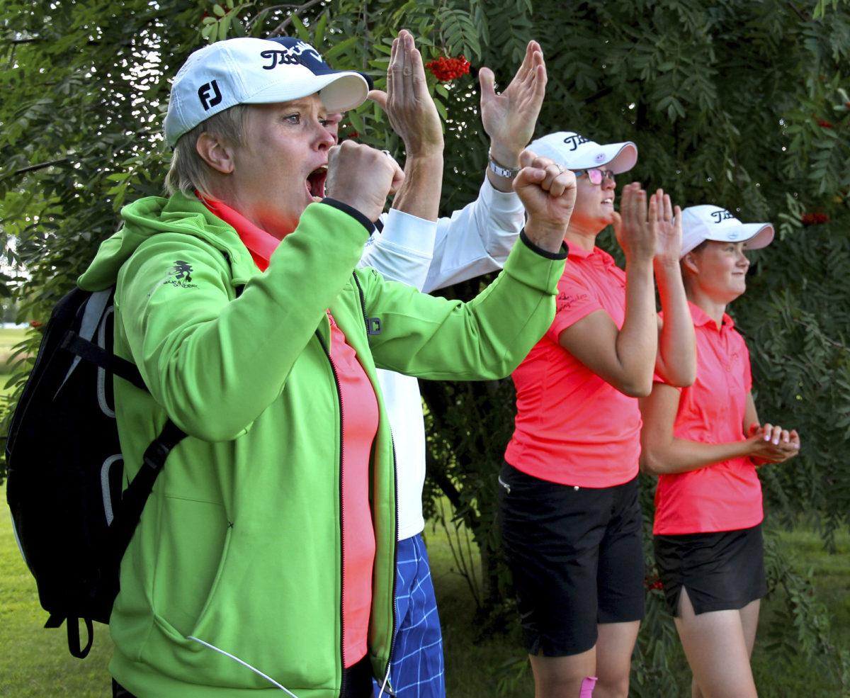 Annamari Pakarinen kannustaa pelaajien ja Koski-Golfin muun taustaryhmän kanssa kentän laidalla.